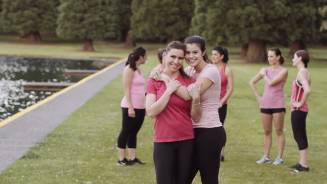 mother and daughter embracing after run for breast cancer awareness - età miste video stock e b–roll