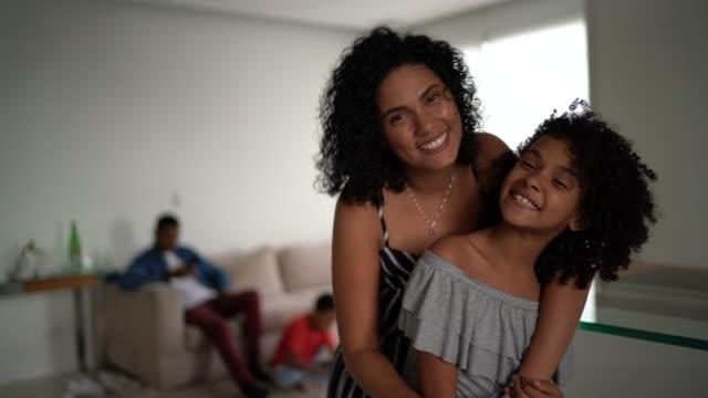 мать и дочь обнимаются дома - портрет - бразилец парду стоковые видео и кадры b-roll