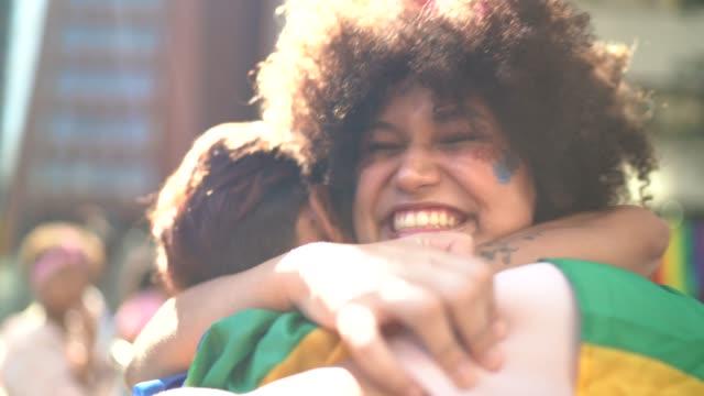 mutter und tochter umarmen sich während der lgbtqi-parade - brasilianischer abstammung stock-videos und b-roll-filmmaterial