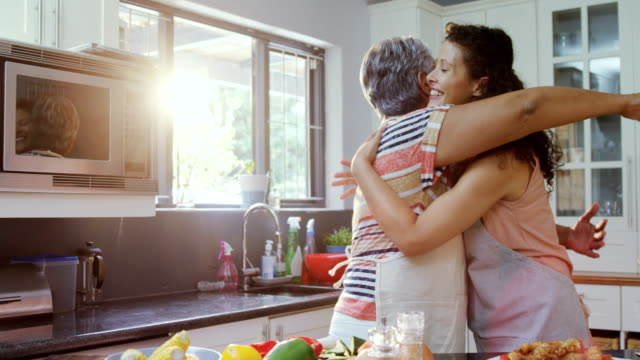 mother and daughter embracing each other in kitchen 4k - origini video stock e b–roll