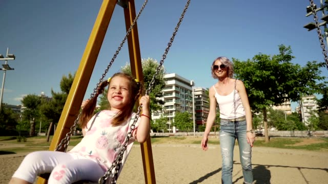Mother and daughter enjoying summer day at a playground Smiling mother is swinging her cute little daughter on swing at a playground. outdoor play equipment stock videos & royalty-free footage