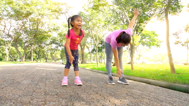 mother and daughter exercising on a park, Slow motion