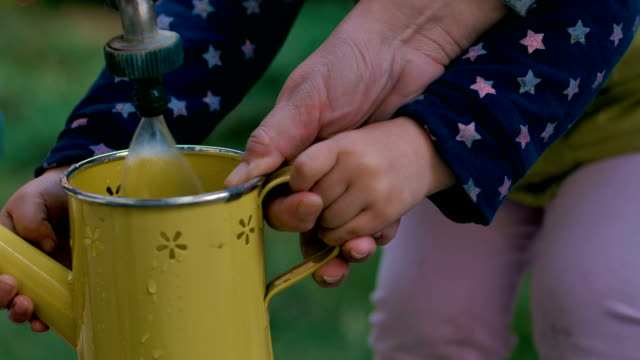 Mother and daughter filling watering can for watering plants in the garden