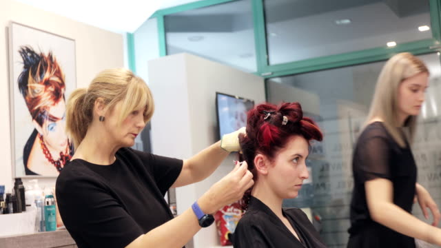 vidéos et rushes de coiffeurs de mère et de descendant travaillant dans leur salon de coiffure - coiffeur