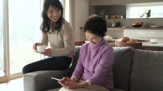 母と娘は、ご自宅でのようなひととき - シニア点の映像素材/bロール