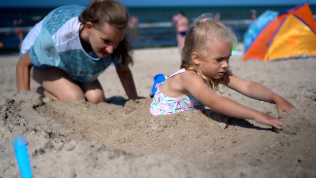 Mother and daughter have fun on seaside. Woman digging little girl deep in sand