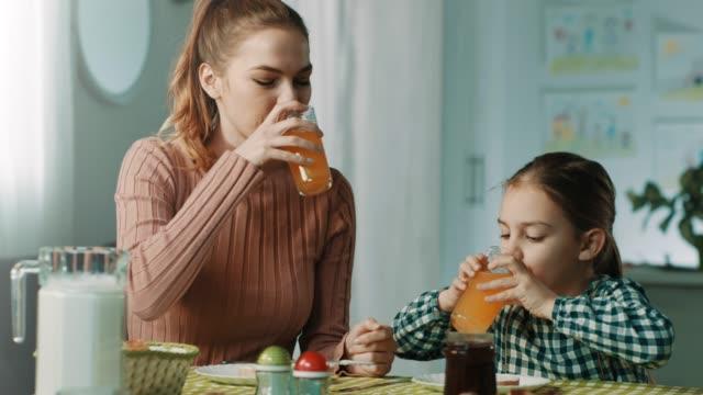 vídeos y material grabado en eventos de stock de madre e hija desayunando en casa - zumo