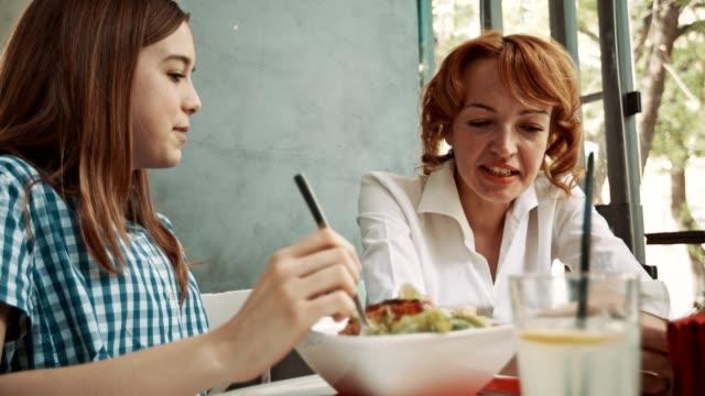 vídeos y material grabado en eventos de stock de madre e hija cenando en el restaurante - madre e hijos