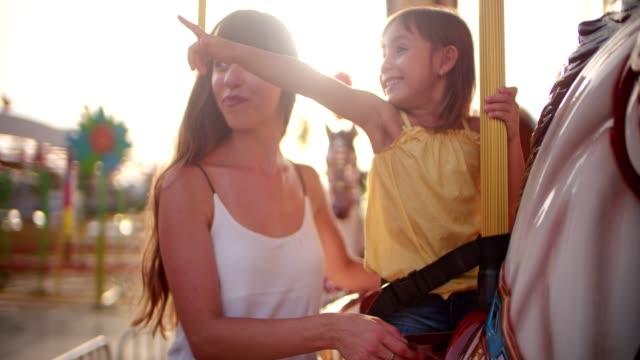 mor och dotter ha kul på carousel rida på sällskapsspel - fritidsanläggning bildbanksvideor och videomaterial från bakom kulisserna