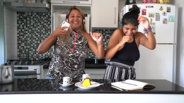 Mother and daughter having fun together while dancing in the kitchen