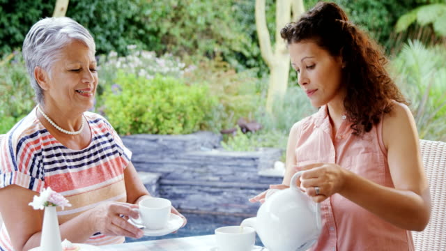 Mother and daughter having tea 4k video