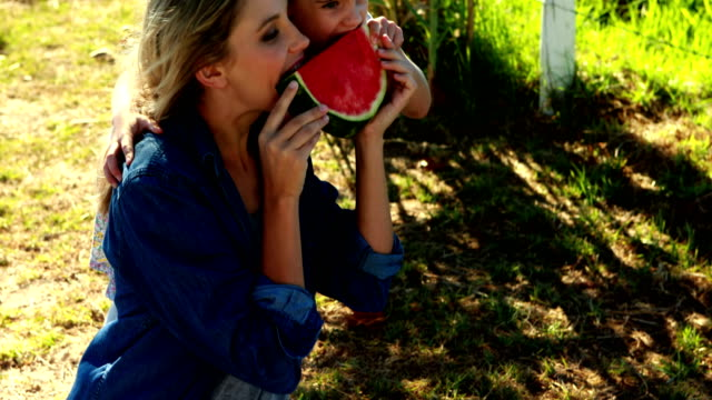 Mother and daughter having watermelon in park 4k video