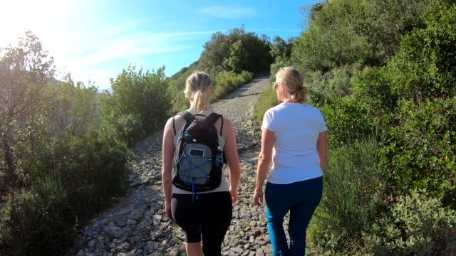 stockvideo's en b-roll-footage met moeder en dochter wandeling langs geplaveide baan, in heuvels - gewone snelheid