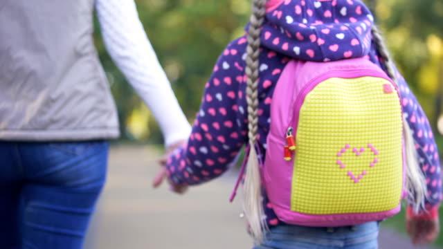 мать и дочь, держась за руки и ходить в дополнительные классы, школьница - ноябрь стоковые видео и кадры b-roll
