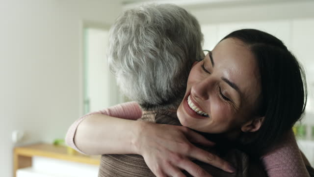 Mother and daughter hugging in living room Senior mother and adult daughter hugging in livig room hug stock videos & royalty-free footage