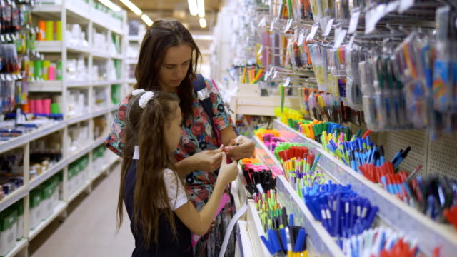 Mother and daughter in a stationery store choose school supplies. Family in supermarket chooses stationery writing pens.