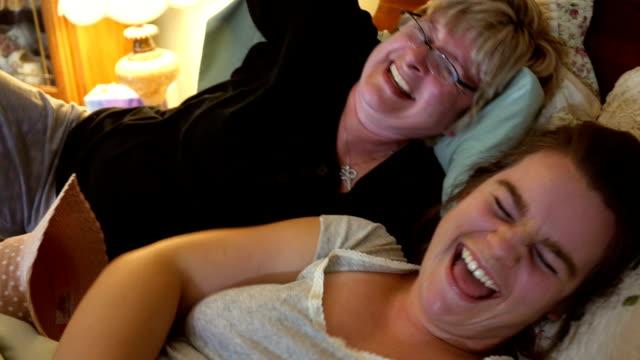 母と娘のベッドでスマート フォン selfie に面白い瞬間を共有します。 - 田舎のライフスタイル点の映像素材/bロール