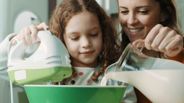 vidéos et rushes de mère et fille dans la cuisine - batteur électrique