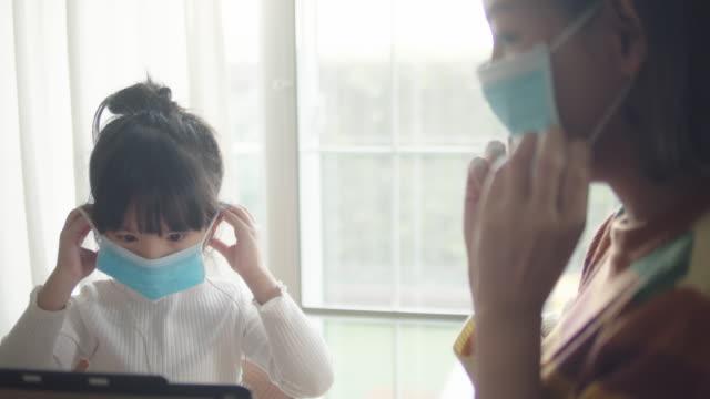 vidéos et rushes de mère et descendant dans le masque médical de protection de visage - enfant masque
