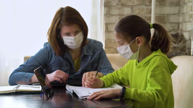 Mother and daughter in medical masks doing homework together video