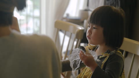 Mother and daughter in the room. Mother and daughter in the room. young girl eating rice ball. childhood stock videos & royalty-free footage