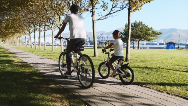 Mother and daughter is riding a bike along the seafront together, steadicam shot A young sporty mother with little daughter riding a bike along the seafront. Steadicam shot of family riding bicycles at sunny morning, rear view. indian family stock videos & royalty-free footage