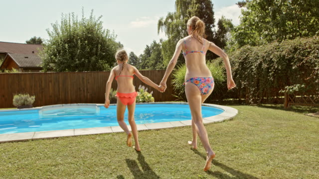SLO MO CS Mother and daughter jumping into the pool video