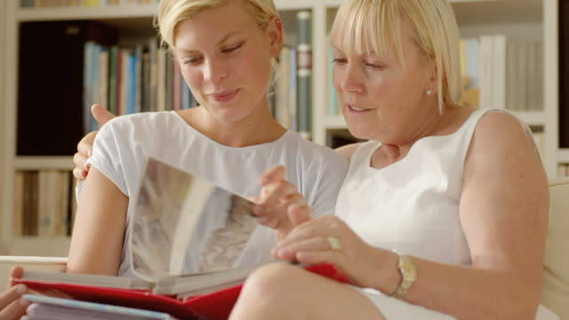 Mother and daughter looking at pictures in photo album Family happiness and memories, happy mother and daughter looking at pictures in photo album at home. souvenir stock videos & royalty-free footage