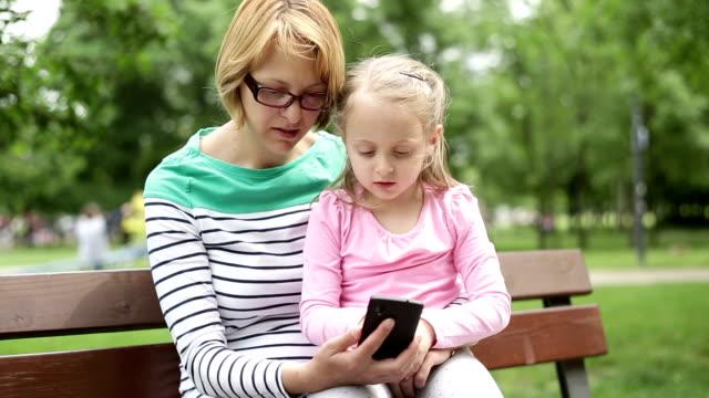 vídeos y material grabado en eventos de stock de madre e hija mirando fotos por teléfono móvil - árboles genealógicos