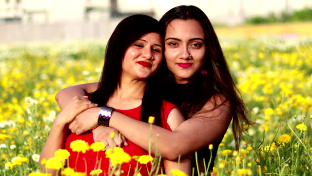 Mother and daughter loving portrait 4K Video : -  Young mother of Indian ethnicity with her younger daughter standing portrait outdoors in the nature during day time. mid adult stock videos & royalty-free footage