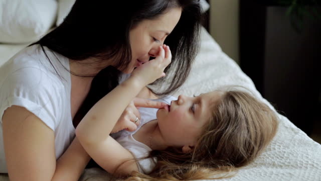 mother and daughter lying and playing on the bed at home - fare il solletico video stock e b–roll