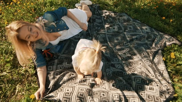 Mother and daughter lying on lawn. Happiness of motherhood and childhood video