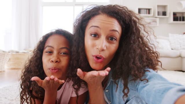mor och dotter liggande på matta och poserar för selfie hemma - blåsa en kyss bildbanksvideor och videomaterial från bakom kulisserna