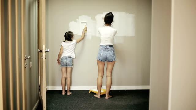 mor och dotter gör reparationer hemma - painting wall bildbanksvideor och videomaterial från bakom kulisserna