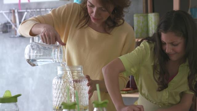 vídeos de stock e filmes b-roll de mother and daughter making a lemonade in teamwork - limonada tradicional