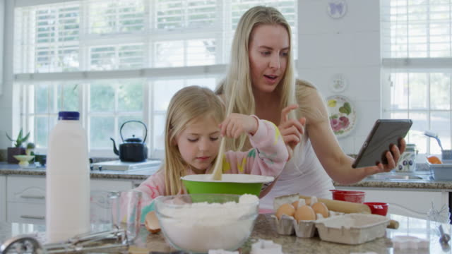 Mother and daughter making christmas cookies at home Front view of a happy young Caucasian mother with her young daughter in their kitchen at Christmas time making cookies, mother following a recipe on a tablet while her daughter stirs ingredients in a mixing bowl recipe stock videos & royalty-free footage