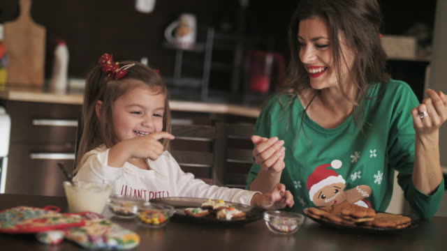 vídeos de stock e filmes b-roll de mother and daughter making christmas cookies together in domestic kitchen, they having fun and decoration sweet cookies. - christmas cookies