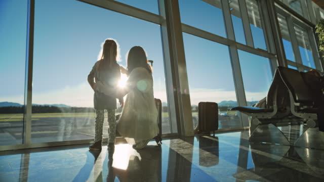 엄마와 딸 공항에서 활주로에 빛나는 태양 관찰 - 공항 스톡 비디오 및 b-롤 화면