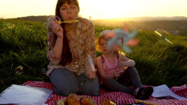 anne ve kızı bir tepe batımında yaz aylarında pikniğe üzerinde. - mountain top stok videoları ve detay görüntü çekimi