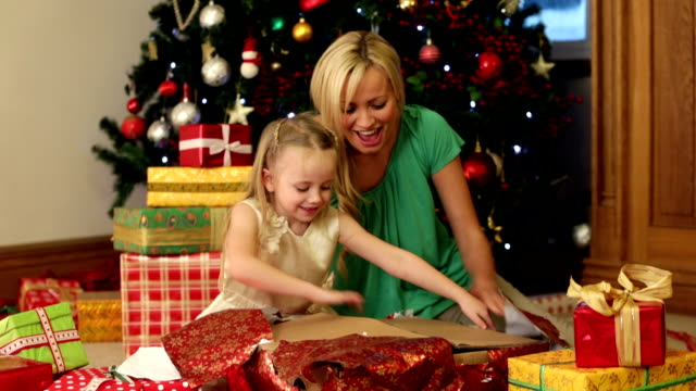 Mother and Daughter On Christmas Morning Mother and daughter sitting on the floor opening a present to find a doll. Little girl hugs the doll and the both smile at camera doll stock videos & royalty-free footage