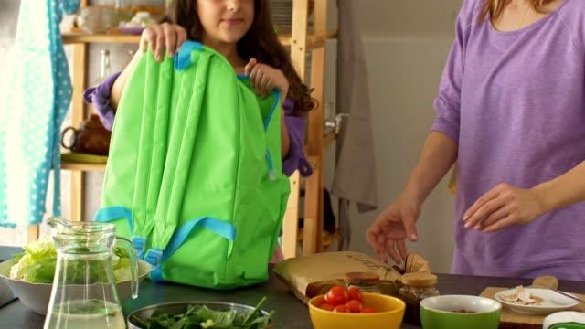 anne ve kızı bir sırt çantası içinde okul öğle yemeği ambalaj - sırt çantası stok videoları ve detay görüntü çekimi