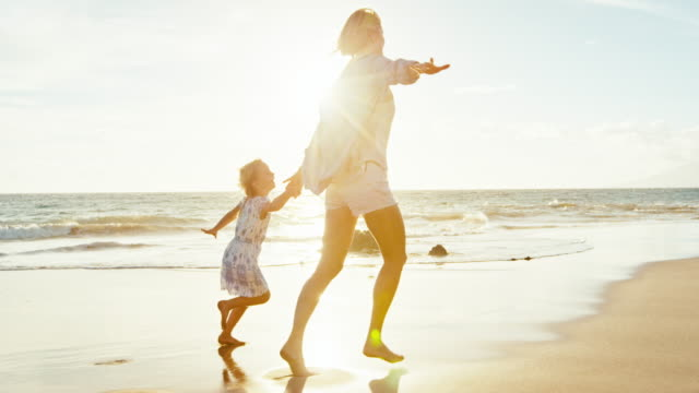 Mãe e filha brincando na praia - vídeo