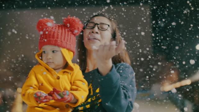 stockvideo's en b-roll-footage met moeder en dochter spelen op winter festival, sneeuwt - family winter holiday