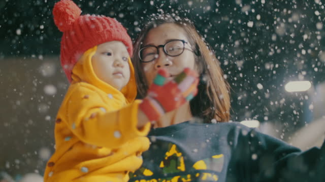 vídeos de stock e filmes b-roll de mother and daughter playing at winter festival, snowing - family christmas