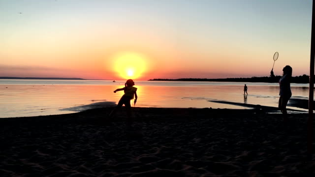 mother and daughter playing badminton at sunset video
