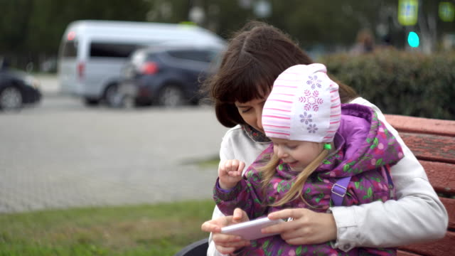 Mother and daughter playing on the smartphone sitting on the bench outdoors. video