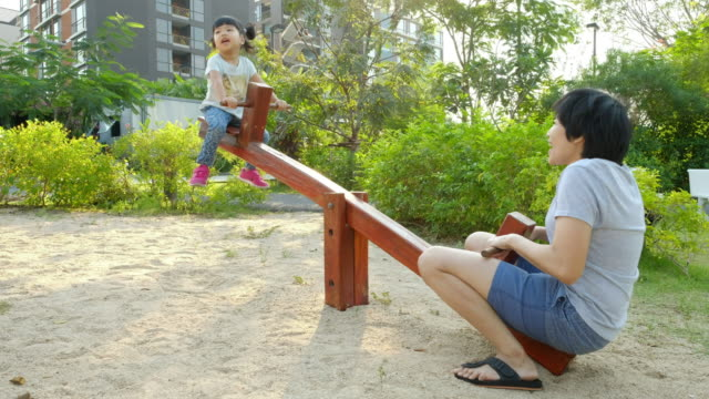 Mother and Daughter playing seesaw at playground video