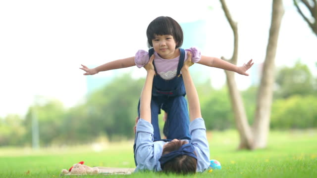 Mother and daughter playing together in yard , arms outstretched
