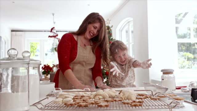 Mother and daughter playing with cookie flour in kitchen Smiling mother and daughter playing with cookie flour at kitchen counter while making Christmas cookies. Baked cookies and muffins on tray for Christmas eve. cookie stock videos & royalty-free footage