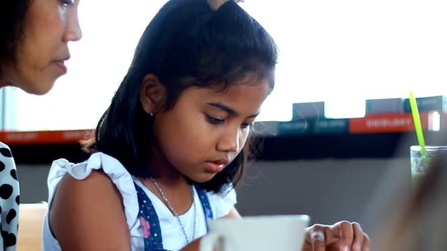 Mother and daughter playing with electronic tablet in cafe video